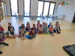 Dzieci siedzą na podłedze