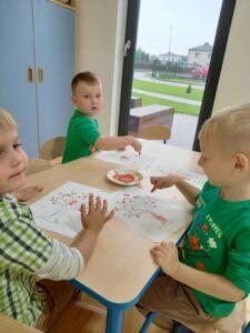 dzieci ryzują farbami drzewo
