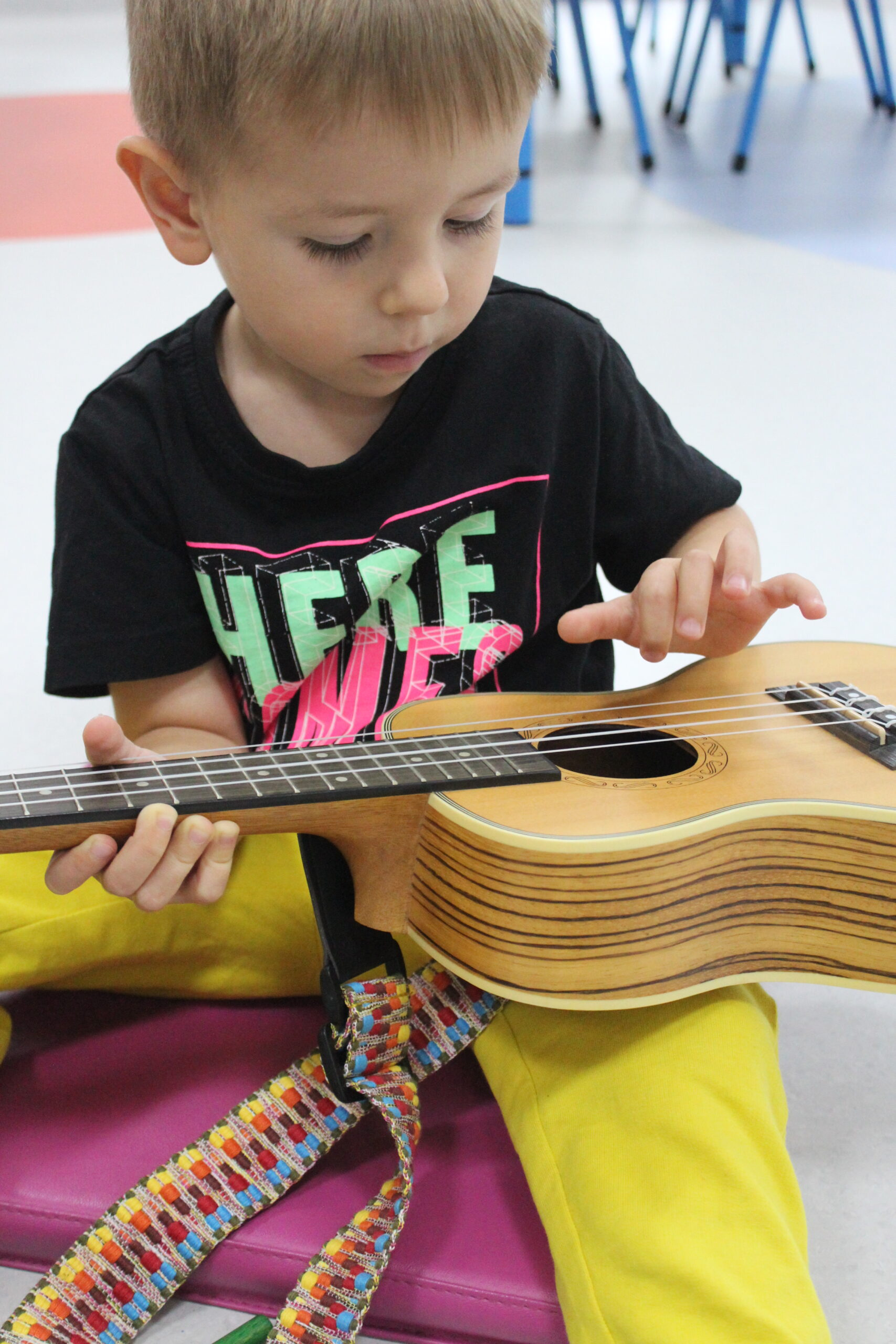 Zdjecie przedstawiające dziecko grające na ukulele