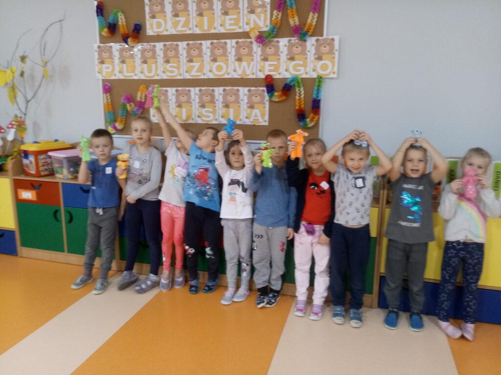 dzieci pod tablicą z pracami plastycznymi
