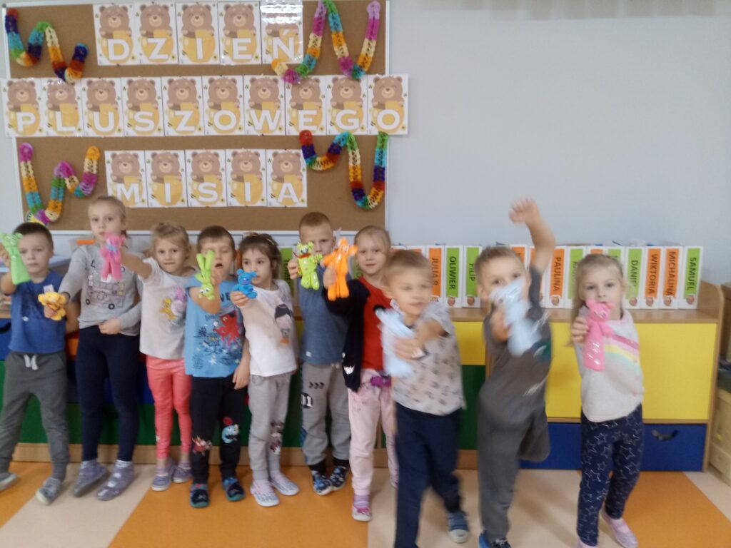 dzieci ustawione w rzędzie prezentujące pracę techniczną- misia