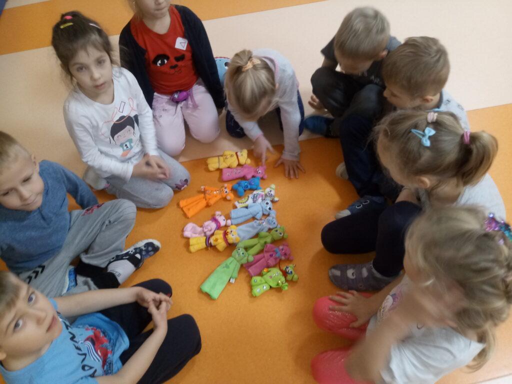 dzieci zgromadzone wokół misiów ze szmatek