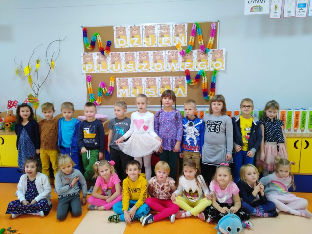 dzieci pod tablicą z pracami plastycznymi na Dzień Misia