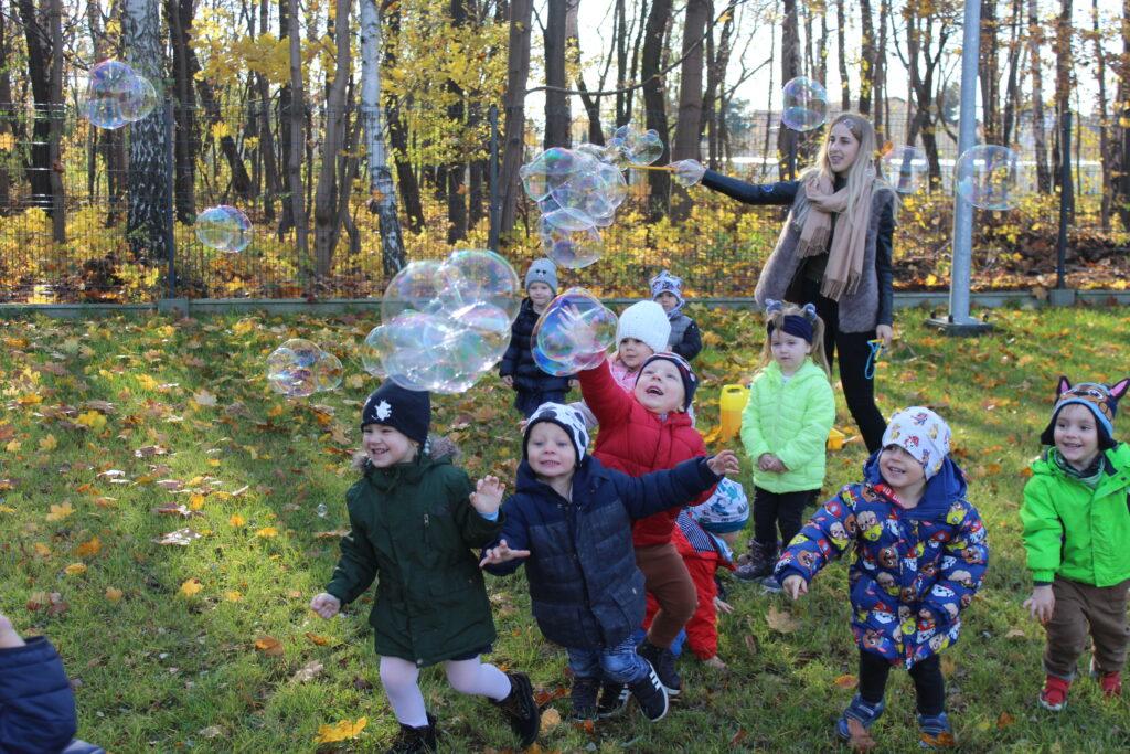 dzieci na podwórku bawią się bańkami